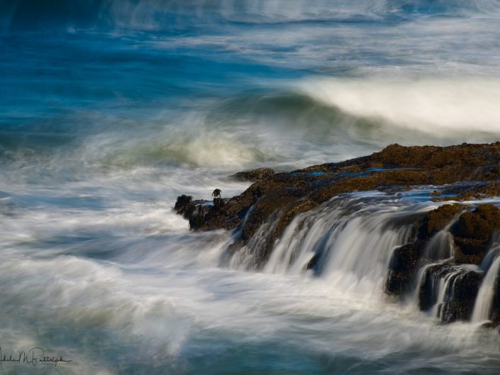 Water flows off of coastal rocks amid a churning ocean at Cape Perpetua, Oregon