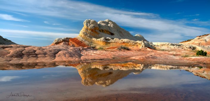 Panoramic photograph of a reflection of a colorful rock knob taken in White Pocket, Vermillion Cliffs National Monument, Arizona.