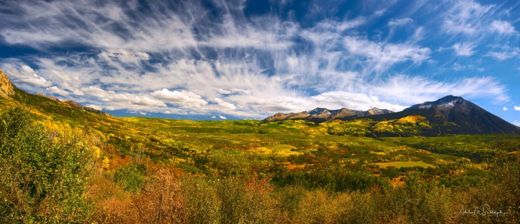 Panoramic photo of autumn on Kebler Pass, Colorado with stunning fall color and dynamic clouds.
