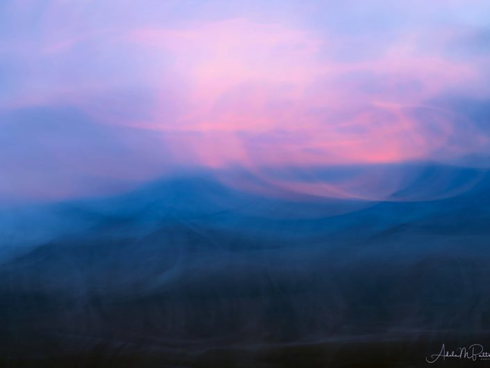 Impressionistic image of a winter dusk at Wallowa Mountains, Oregon. Pink clouds swirl about a soft blue.