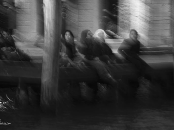 Black and white motion blur image of people sitting on a dock along the Grand Canal in Venice, Italy.