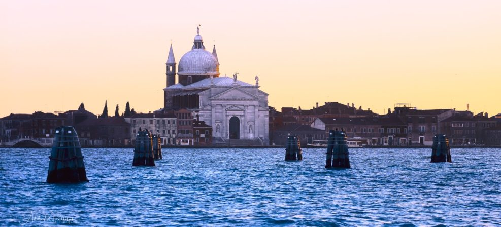 View of Church of San Giorgio Maggiore across the water at sunset. Image taken in Venice, Italy.