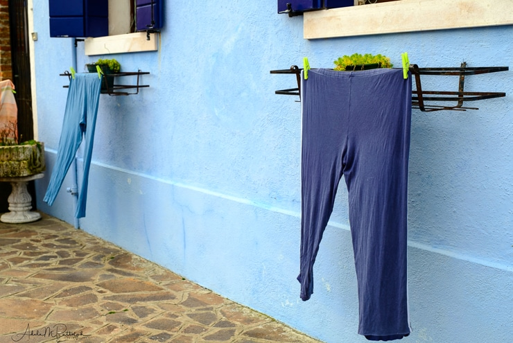 Two pair of blue pants hang from plant stands on the side of a blue wall in Burano, Italy.