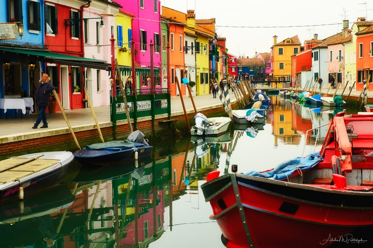Colorful buildings and boats line a canal in Burano, Italy