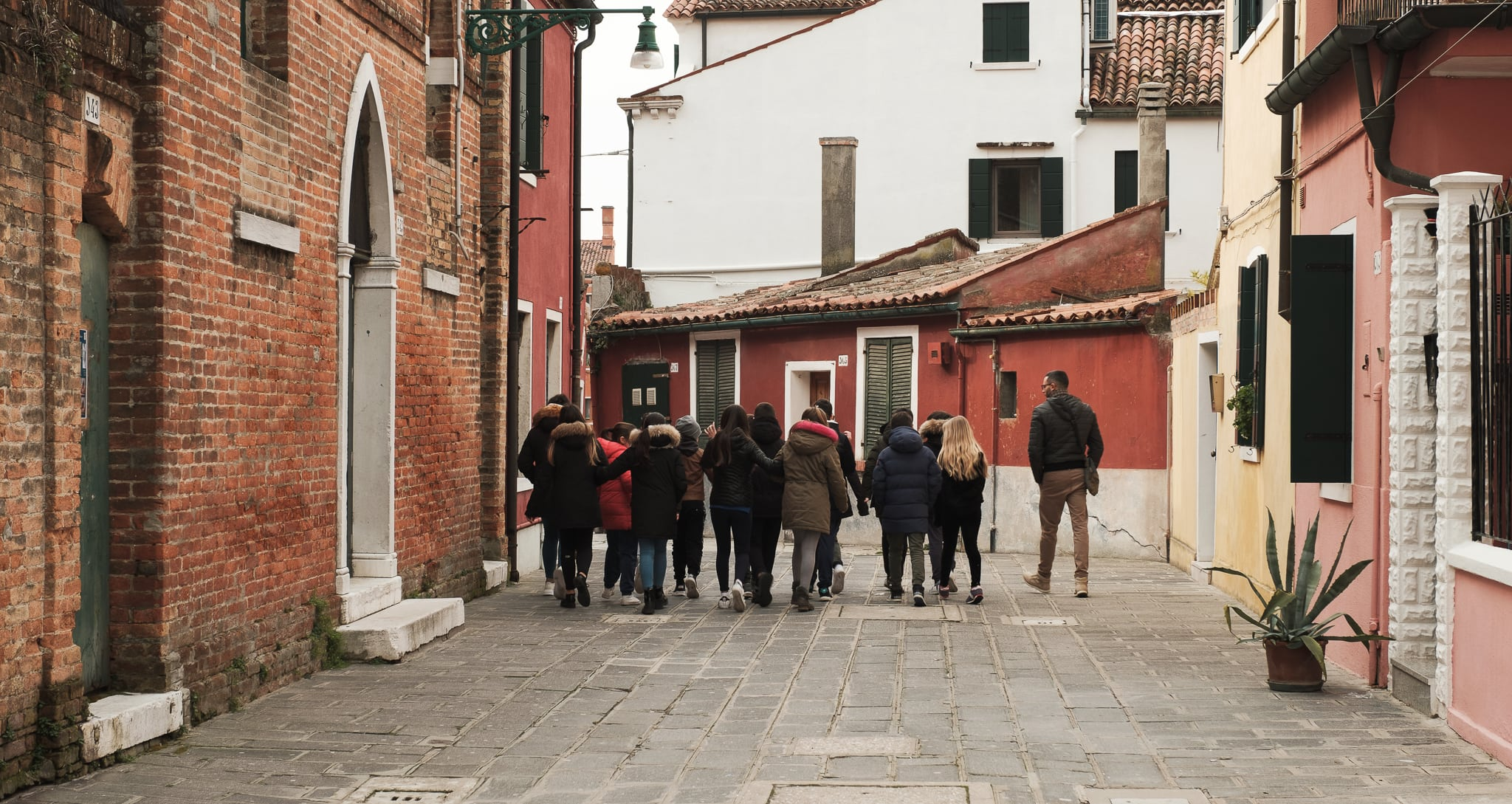 A group of school children and their teacher walking in Burano, Italy.