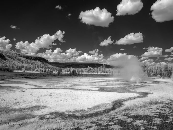 Black and white infrared photograph of erupting geysers and surrounding landscape. Shot in the Black Sand Geyser Basin, Yellowstone National Park, Wyoming.