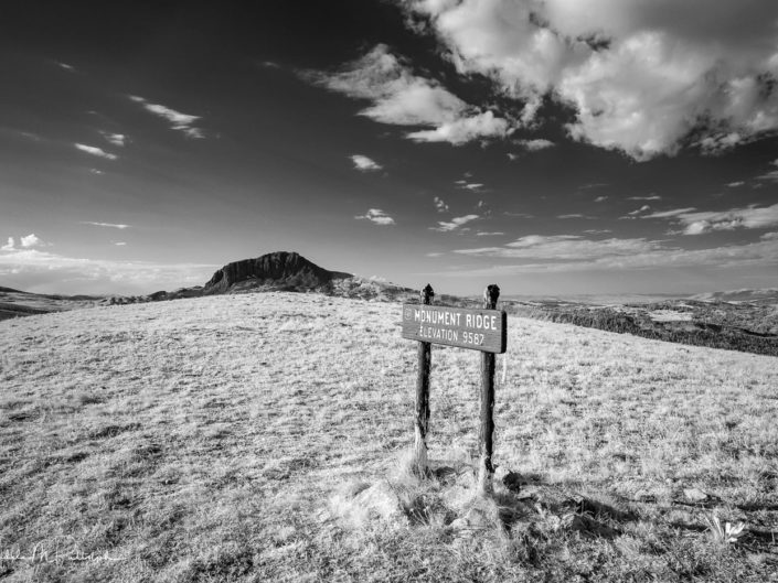 Black and white infrared photograph of the top of Monument Ridge located in the Gravelly Range, Montana. Image includes elevation sign in the foreground.